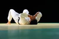 畳の上に横たわる日本人の男子柔道選手
