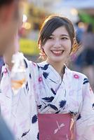 すくった金魚を見せる浴衣の日本人女性