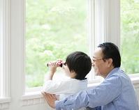 窓辺から遠くを見る祖父と孫