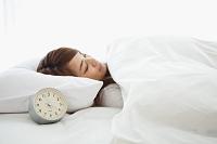 眠る日本人女性と目覚まし時計