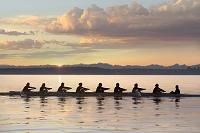 夕焼けの中ボートを漕ぐチーム