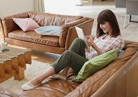 ソファに座ってタブレットを操作する日本人女性