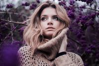 紫色の花とニットを着た女性