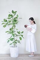 観葉植物横に立つ赤ちゃんを抱いた母親