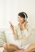 スマートフォンで音楽を聴く笑顔の20代日本人女性
