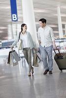空港で荷物を運ぶカップル