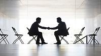 オフィスで握手をする男性シルエット