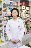 薬の商品棚の前に立つ日本人女性薬剤師