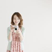 カメラを持ち微笑む女性