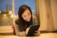 カーペットに横たわってタブレットを見る日本人女性