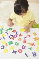 アルファベットのパズルで遊ぶ女の子