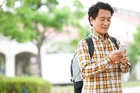 スマートフォンを操作する中年日本人男性