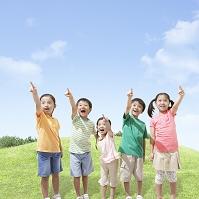 草原で指を指す日本人の子供達
