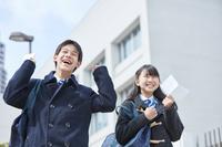 受験票を持って喜ぶ男女の中学生