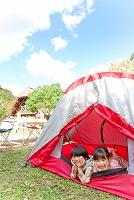 テントで寝転んでほおづえをつく男の子と女の子