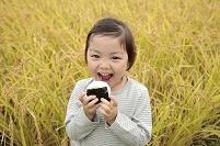 田園でおにぎりを食べる日本人の女の子