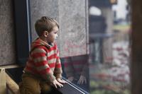 窓辺から遠くを見る子供