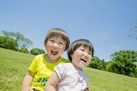 新緑の公園で遊ぶ兄と妹