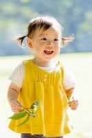 公園でドングリを持って笑う女の子