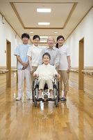 家族と介護施設スタッフに囲まれる車椅子のシニア女性