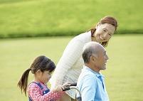 車椅子に乗るシニア男性と家族