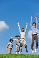 ジャンプしている笑顔の日本人家族