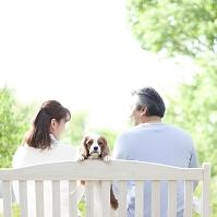 ベンチに座る夫婦と犬