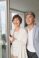 窓辺から遠くを見る日本人のシニア夫婦