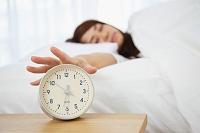 目覚まし時計に手を伸ばす日本人女性