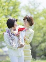 花束を持つ母と寄り添う娘
