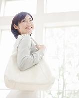 バッグを肩にかけて振り返る女性