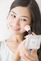 鏡を見てメイクする日本人女性