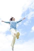 手を広げてジャンプする若い日本人女性