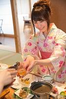 旅館の食事でビールを注ぐ浴衣の女性