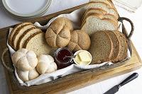 バスケットに入った様々なパンとジャムとバター