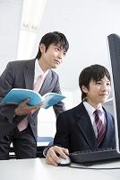 パソコンを学ぶ男子中学生と指導する教師