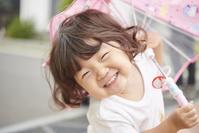 傘をさす笑顔の日本人の女の子