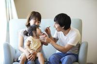 娘にアイスを食べさせる父親