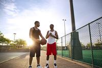 友人とバスケをする若者