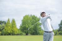 ゴルフをする中高年男性