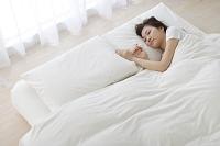 ベッドで眠る若い日本人女性