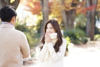 秋の並木道で談笑する20代カップル