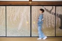 襖絵の前を歩く着物の日本人女性