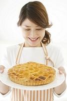 アップルパイを差し出す若い女性