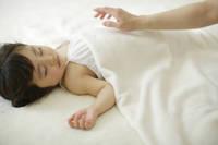 白いブランケットの上で眠る幼い女の子