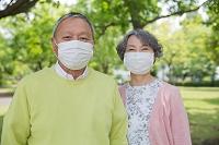 公園でマスクを着用している老夫婦