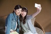 スマートフォンで撮影する若い日本人女性