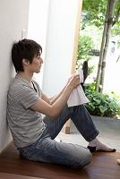 壁にもたれて靴を磨く日本人男性