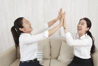 ハイタッチして喜ぶビジネス女性