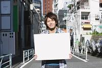 街角でホワイトボードを持つ日本人男性